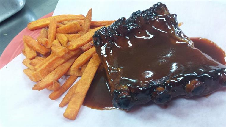 half rack of ribs covered in barbecue sauce with french fries on the side.