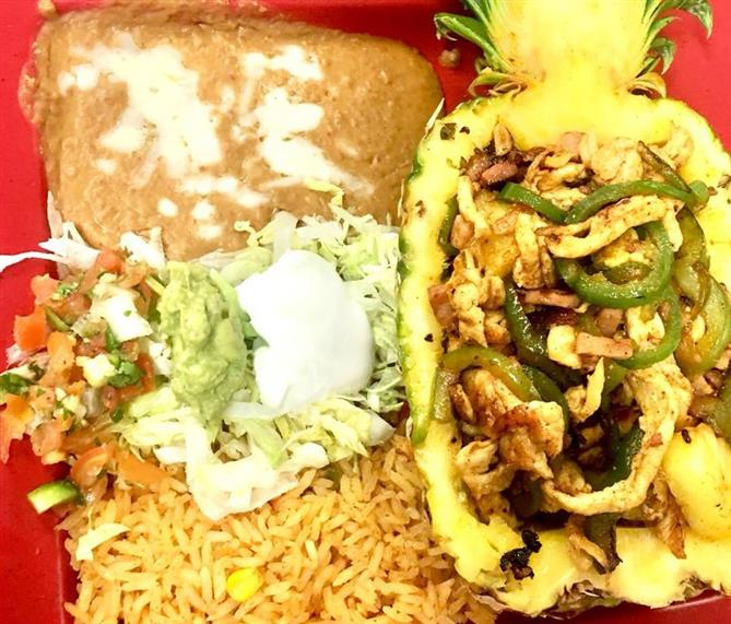 Seasoned chicken sliced andsaueed with peppers and onions. Served in a pineapple with rice, beans, salad and guacamole on the side.