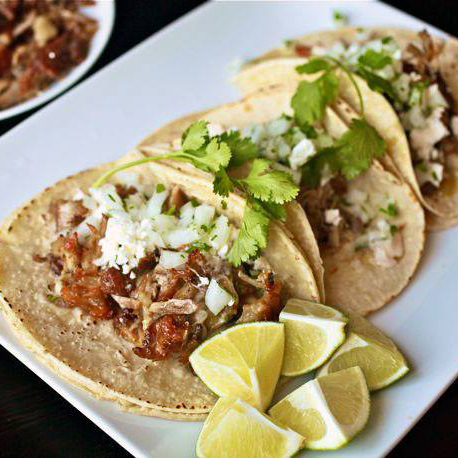 Soft tacos filled with pulled chicken, diced onion, and cilantro