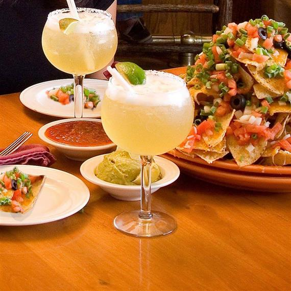 Two Margaritas on a table with nachos on the side