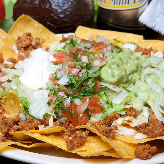 Nachos covered in cheese, beef, sour cream and lettuce