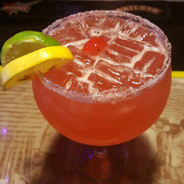 A margarita with a cherry, lemon, and lime wedges on the wedge of the glass
