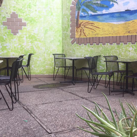 Empty tables with chairs and a painting on the wall behind them