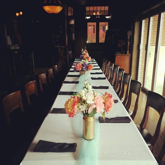 a long table set for a private event swith flowers in the middle of the table
