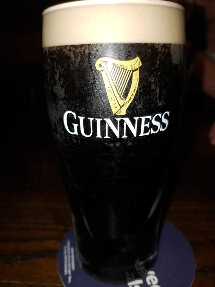 A glass of beer with the Guinness logo