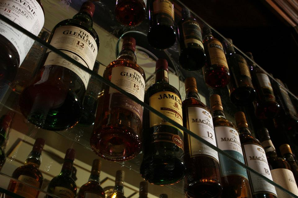 A view form underneath a glass shelf filled with Whiskey bottles