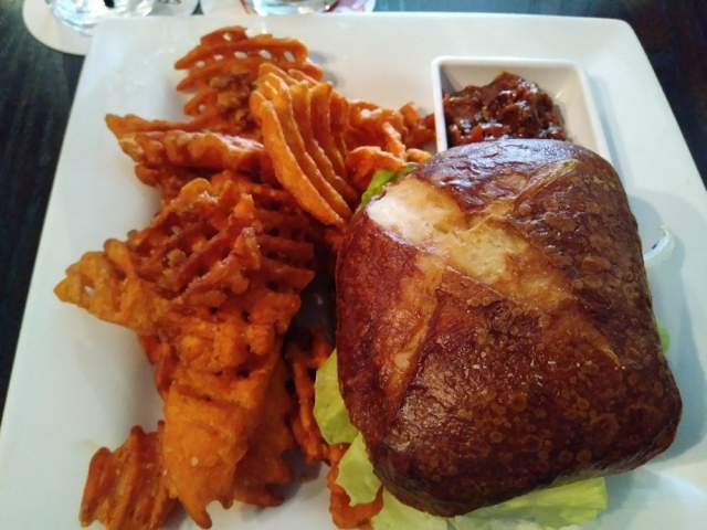 A sandwich with waffle sweet potato fries on the side