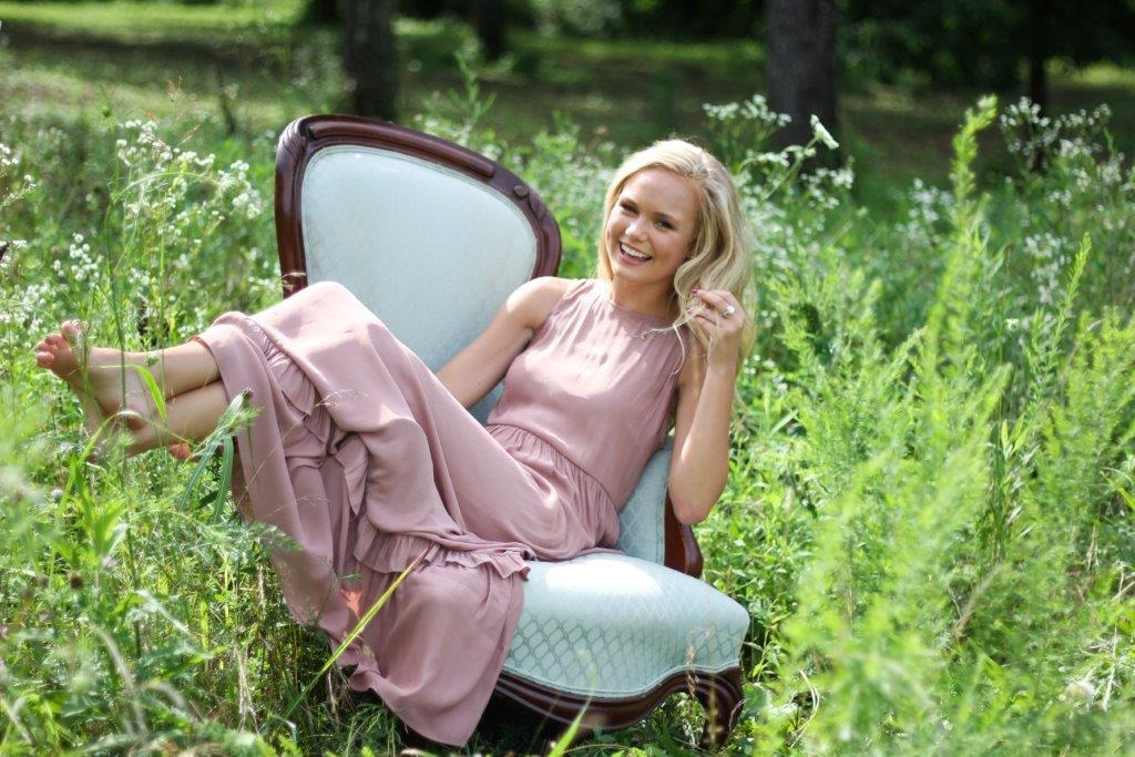 Taylor Rae smiling and sitting in a vintage style chair outside in a field of flowers.