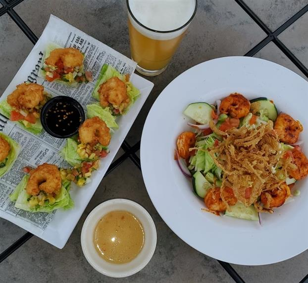 A salad with lettuce, fried onions, cucumbers, onion, and tomatoes next to fried shrimp over lettuce cups.