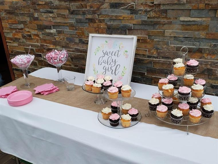 "A table of candy and cupcakes with a sign that says ""Sweet Baby Girl"""