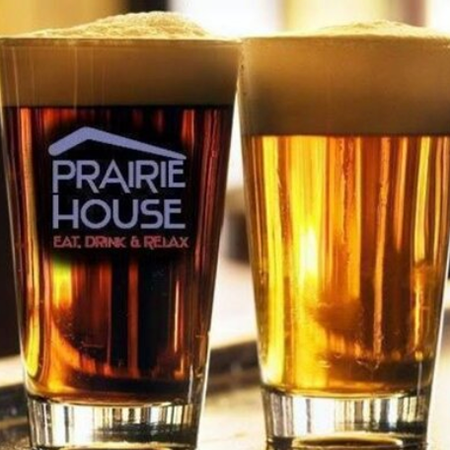 Two glasses of beer. One glass has the Prairie House logo on the front of it