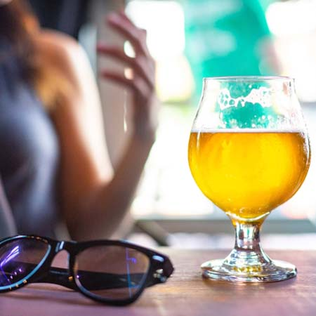 A glass of beer on the bar next to sunglasses