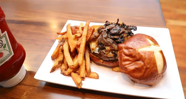 A burger with sauteed mushrooms, onions, and swiss cheese with a side of fries