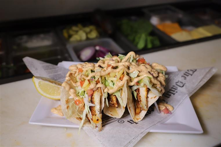 soft tacos with chicken, lettuce, and a creamy sauce drizzled on top