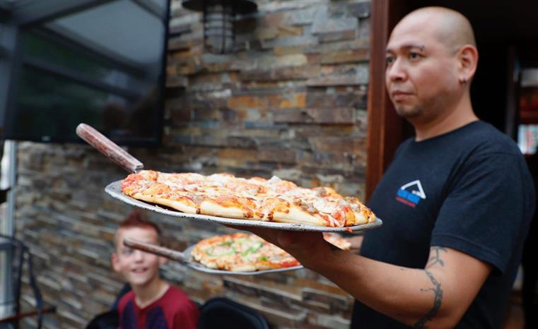 A server holding two trays of round pizzas for a private event