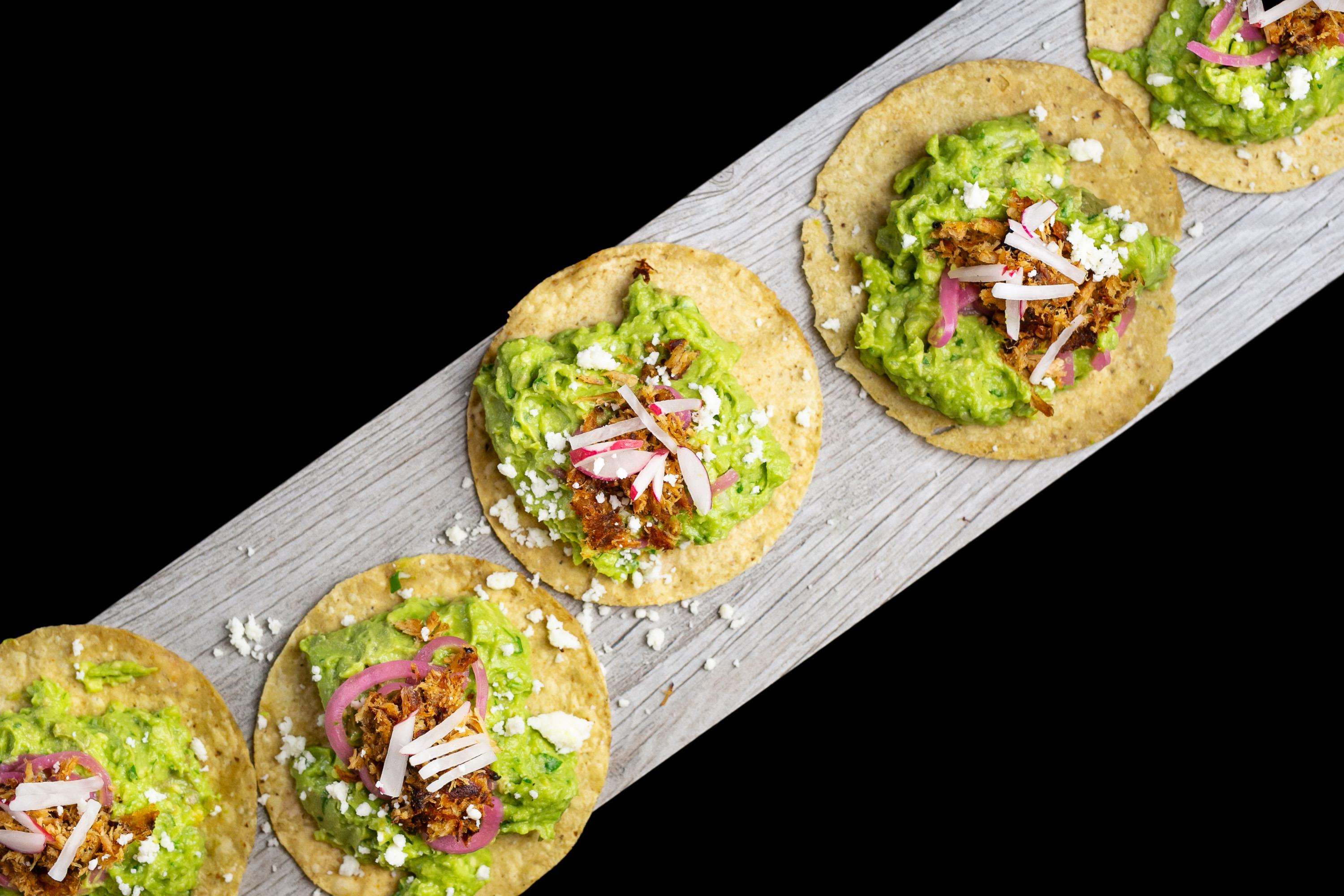 several tortillas with guacamole and various toppings