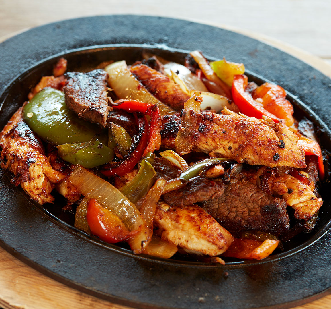 chicken and vegetable fajita in cast iron pan in wooden holder