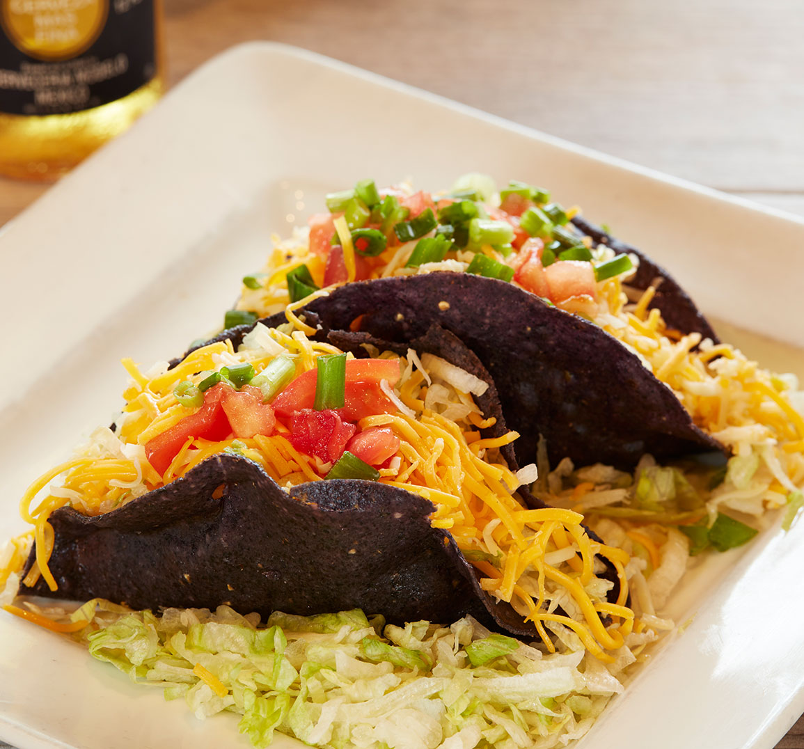 Blue corn taco with shredded cheese, diced tomatoes, and jalapenos