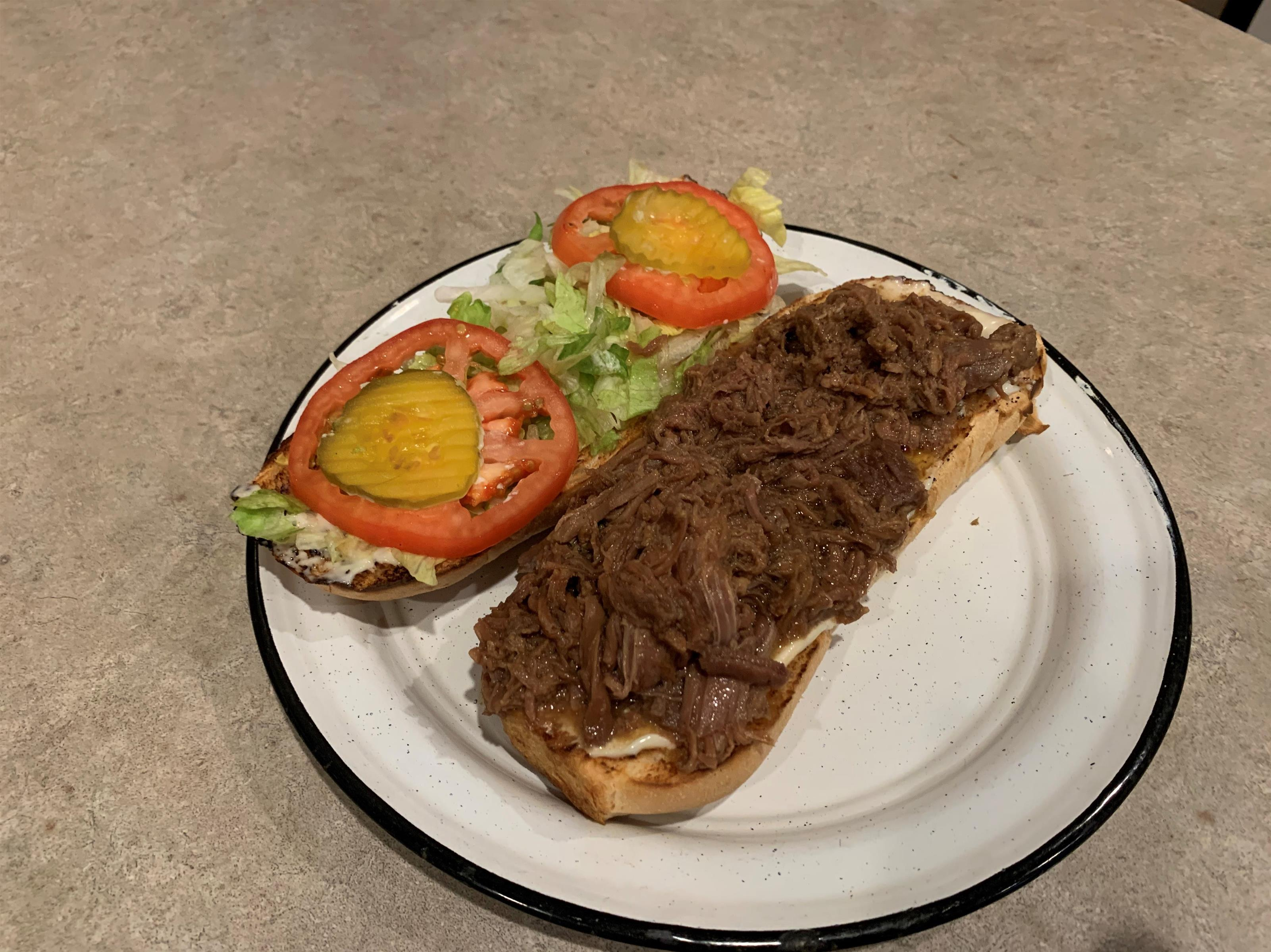 Pulled pork poboy fully dressed with lettuce tomato and mayo