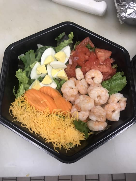 Premade salad with shrimp, eggs, tomatoes, cheese over a bed of lettuce