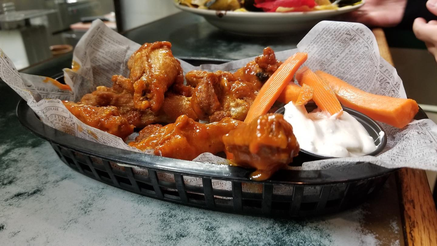 Saucy buffalo wings in basket with carrot sticks
