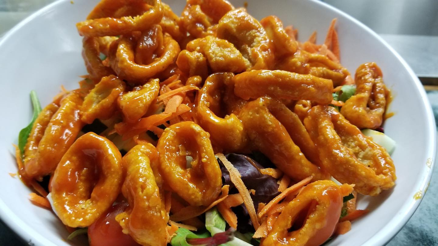 Thai chili calamari in bowl over greens