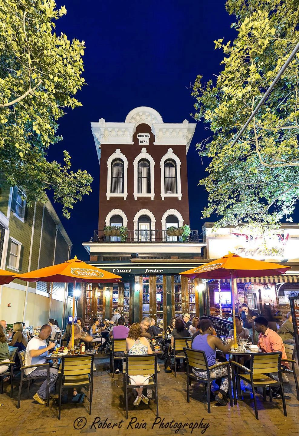 Tall 3 story brick building with outdoor patio filled with people eating