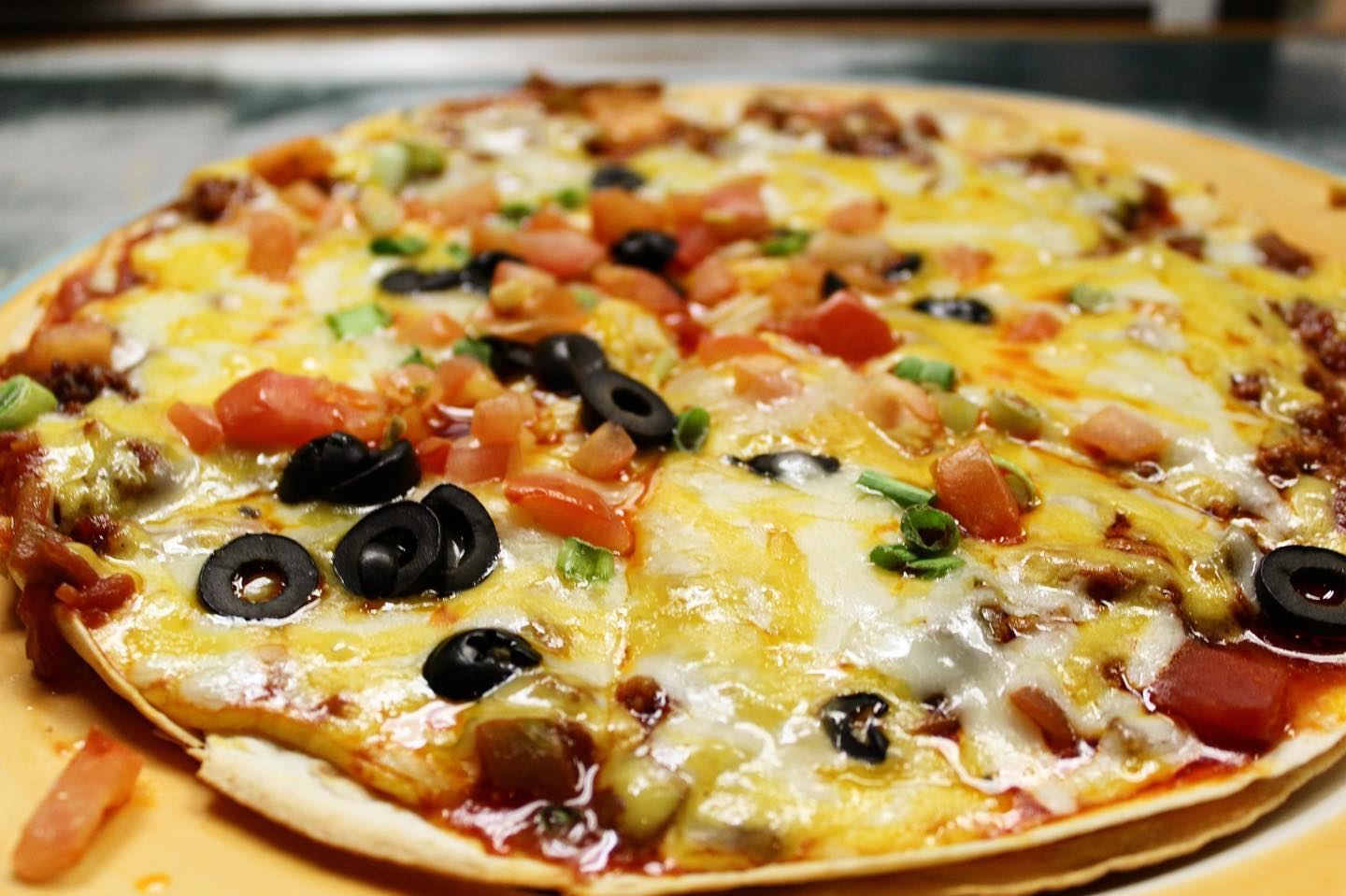 Cheesy pizza with olive and tomato slices