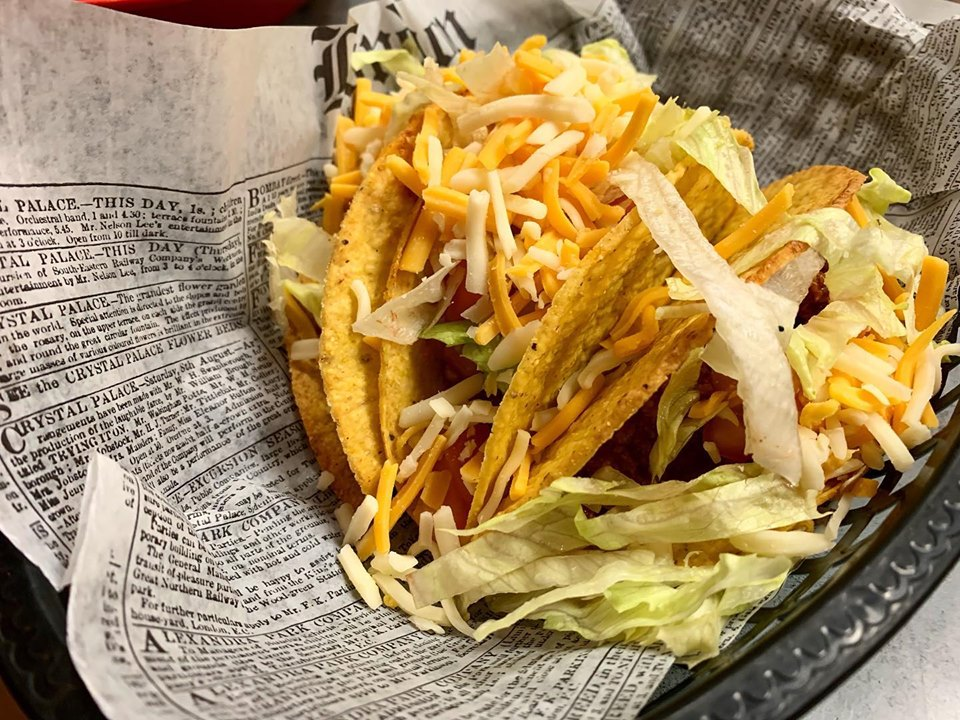 Hard tacos with shredded cheese and lettuce in basket