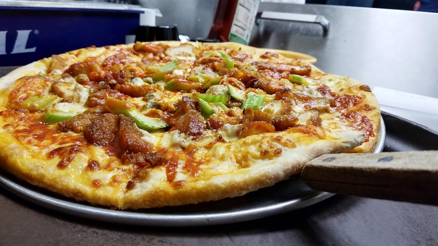 Pizza with diced meat and sauce and avocado on pizza paddle
