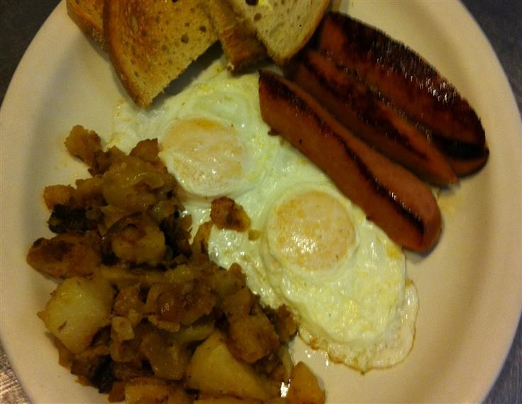 two eggs cooked over easy with homefries, sausage and toast