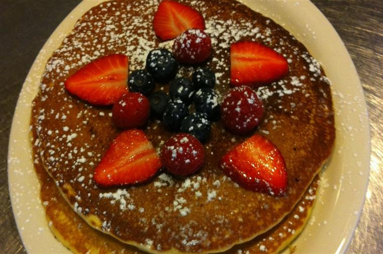 stack of pancakes topped with strawberries, blueberries and powdered sugar