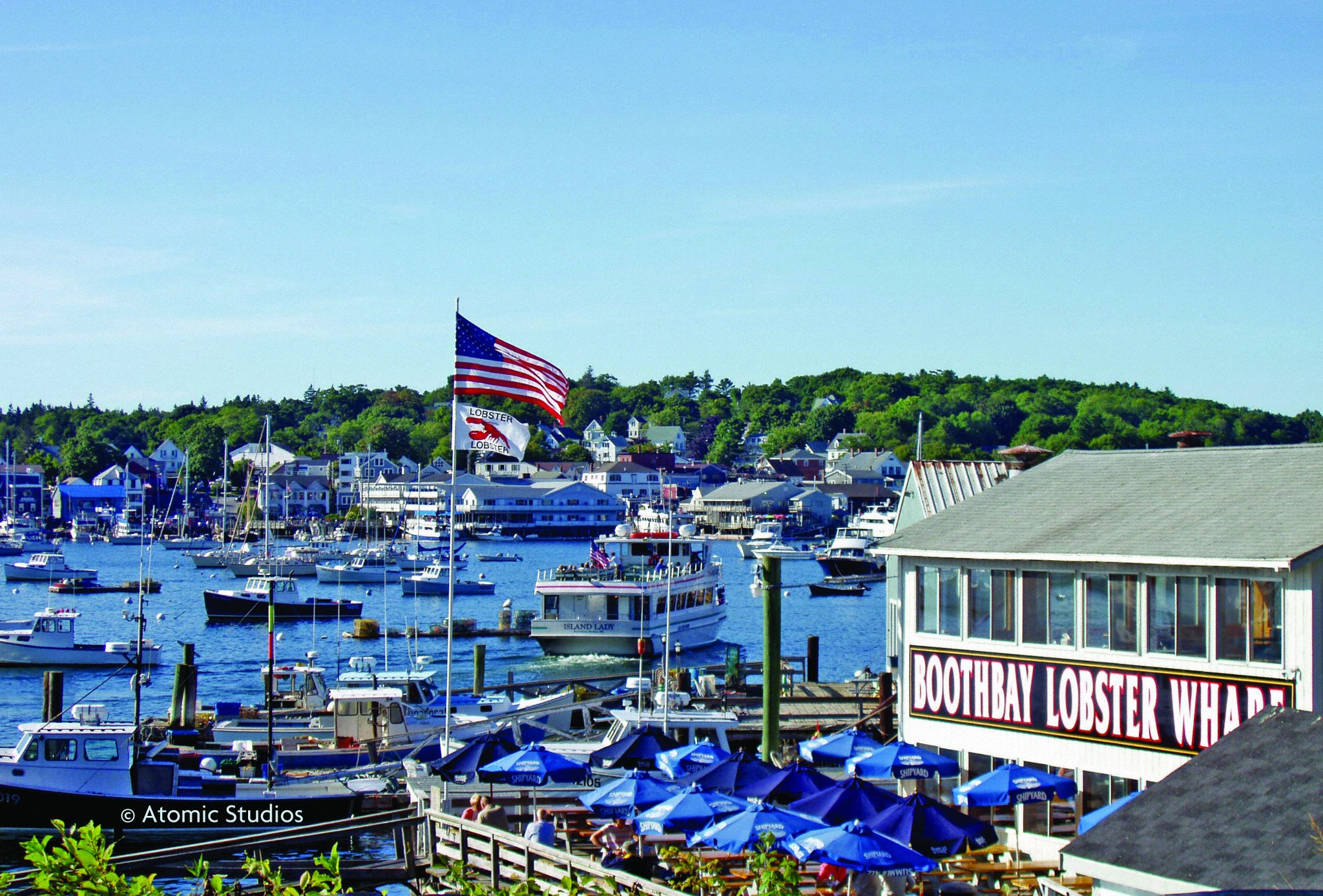 Lobster wharf with many fishing boats in water and dockside restaurant
