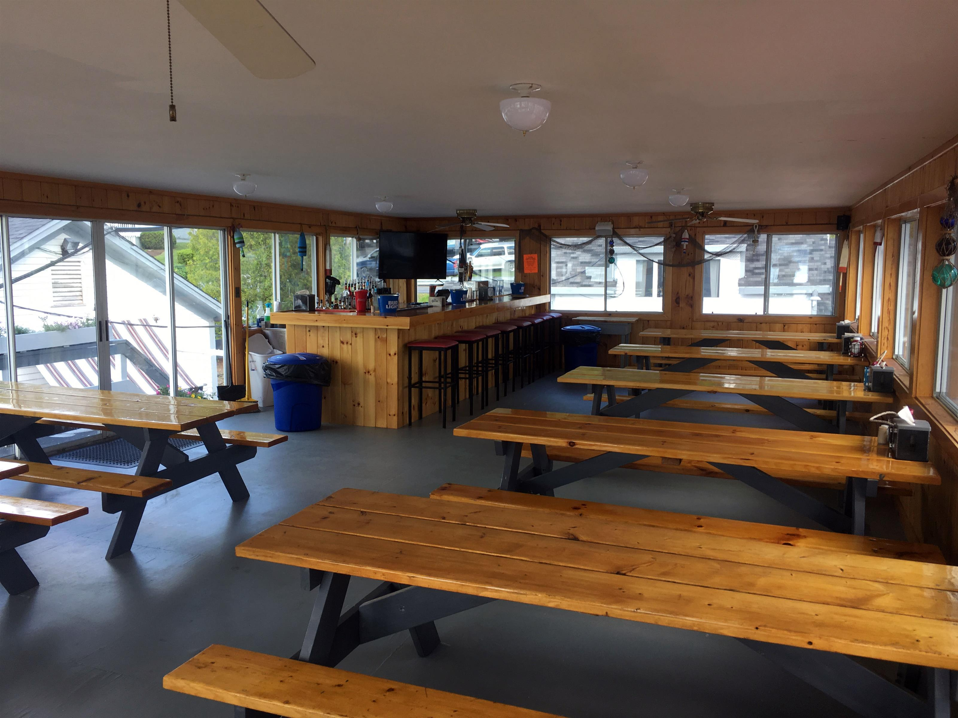 Room with empty wooden picnic tables next to wooden bar
