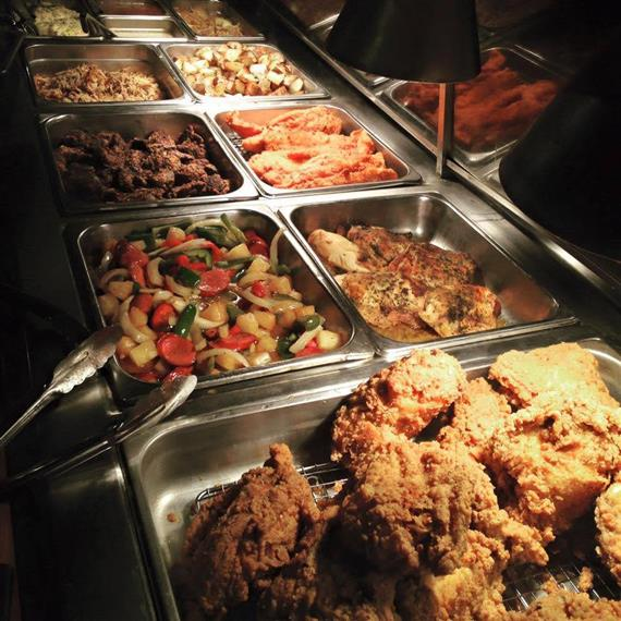 assortment of buffet options laid out in trays with serving tongs