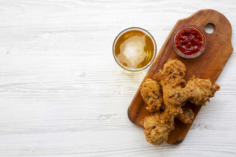 fried chicken wings on a wooden board with dipping sauce and a glass of beer
