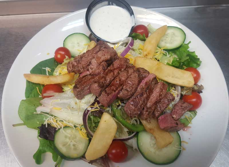 grilled steak salad with cucumbers, lettuce, tomatoes topped with fries