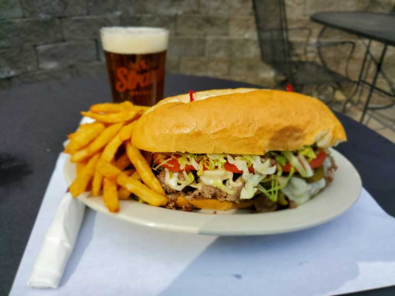 grilled chicken sandwich topped with lettuce, tomatoes, cheese with a side of fries and a beer