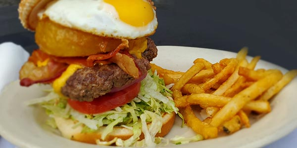 cheeseburger topped with bacon, lettuce, tomato, onion ring, and a fried egg with a side of fries