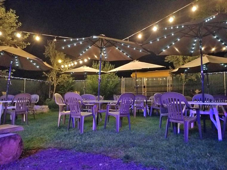 Outdoor seating at night with string lights, tables, and umbrellas