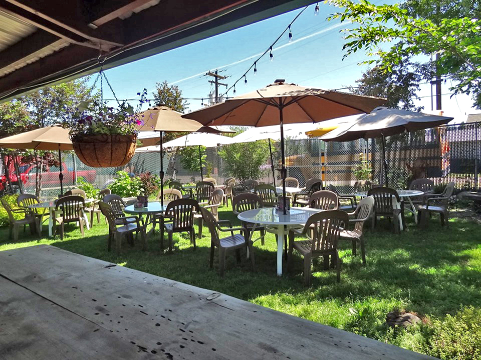 outdoor seating area with string lights, tables with umbrellas, and a bar area with an overhang