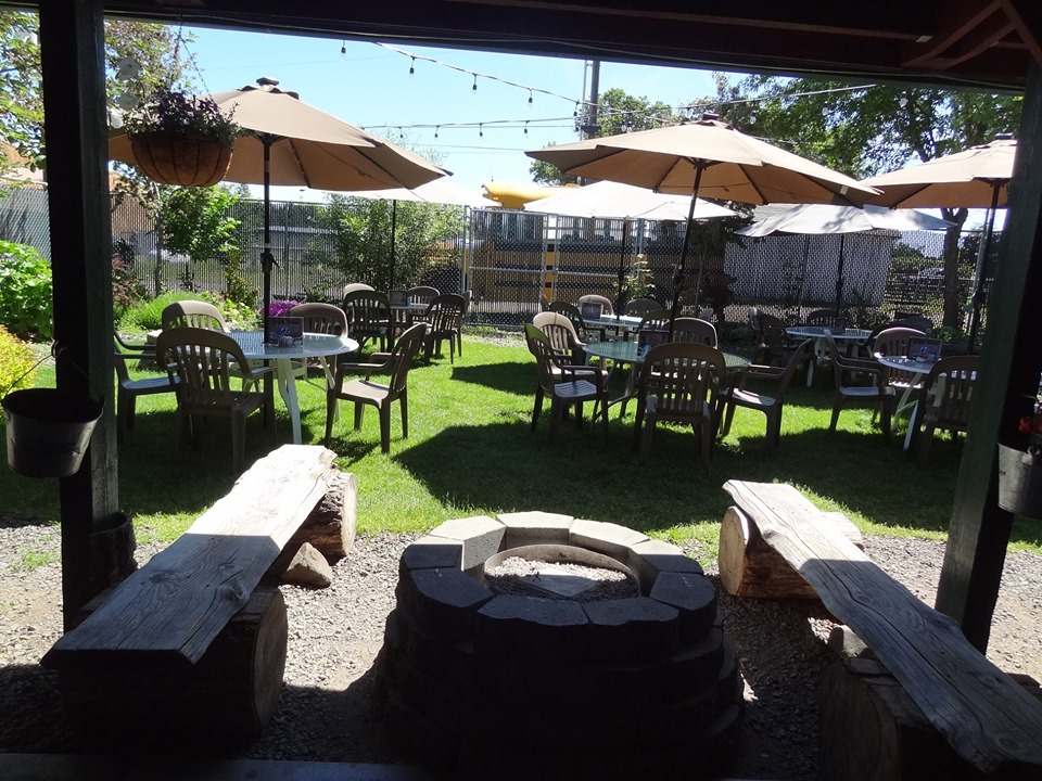 Outdoor seating area during the day with umbrellas and set tables with chairs.