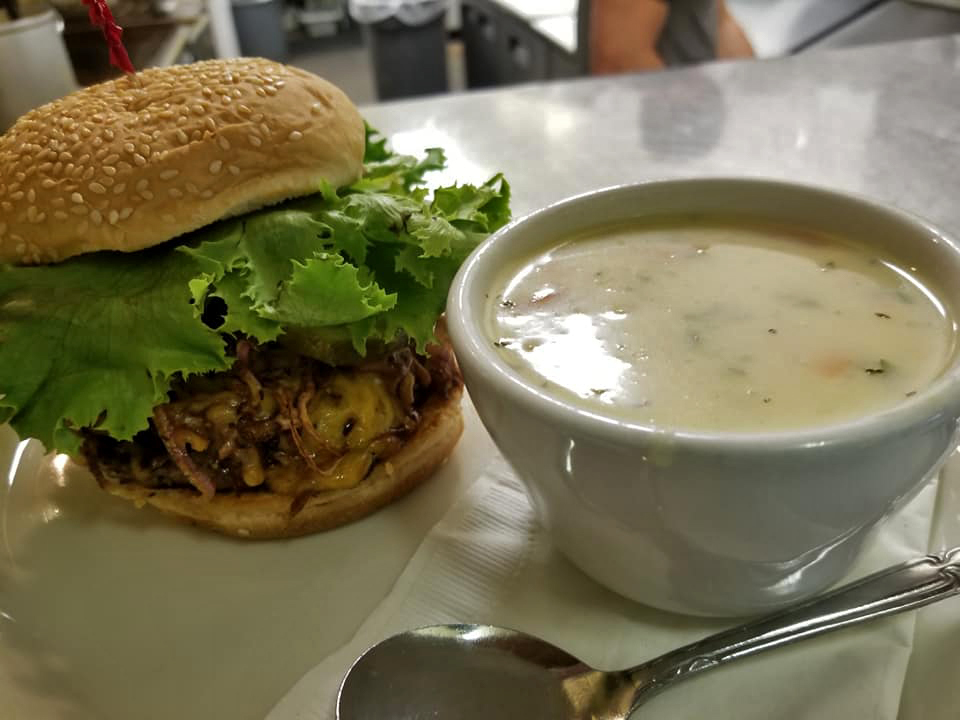 A cheeseburger with fried onions, and lettuce with a side of creamy soup
