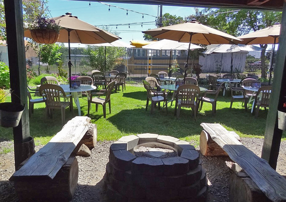 The outdoor seating area during the day with string lights, tables, and umbrellas