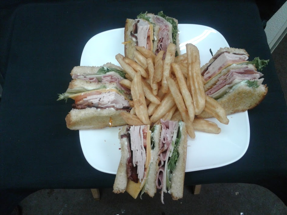 A triple decker of thinly sliced turkey breast, ham, crisp bacon, Swiss and Cheddar cheese, lettuce, tomatoes and mayo served on toasted sourdough with a side of french fries.