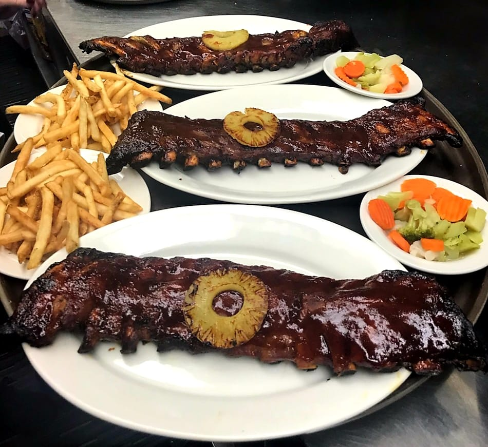three full racks of ribs topped with barbecue sauce and a pineapple slice. French fries and mixed vegetables on the side.