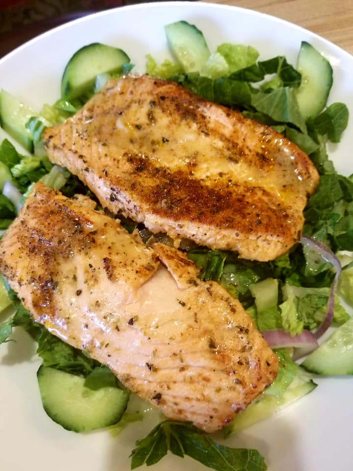 two pieces of  grilled chicken over a bed of greens