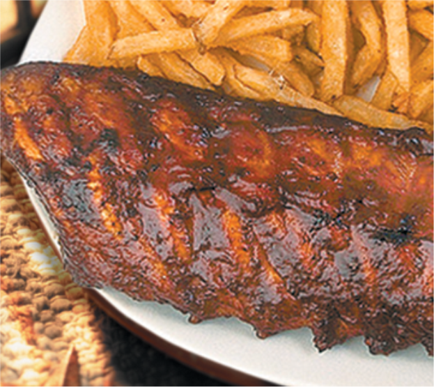 full rack of ribs covered in barbecue sauce. french fries on the side.