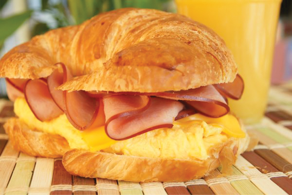 ham, eggs, and cheese on a croissant with a glass of orange juice.
