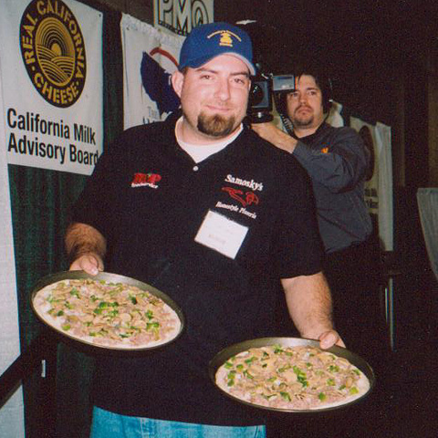 Jason holding up two pizza pies at a competition